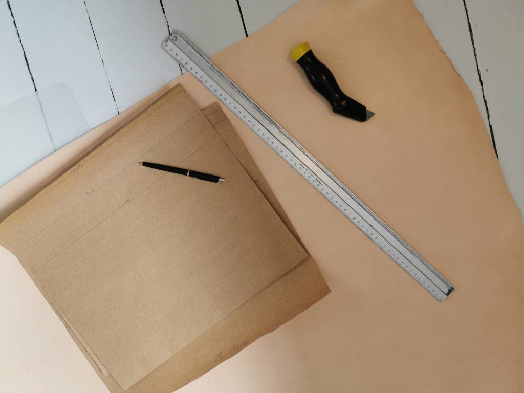 Mønsterpapir, lineal og hobbykniv ligger på skind